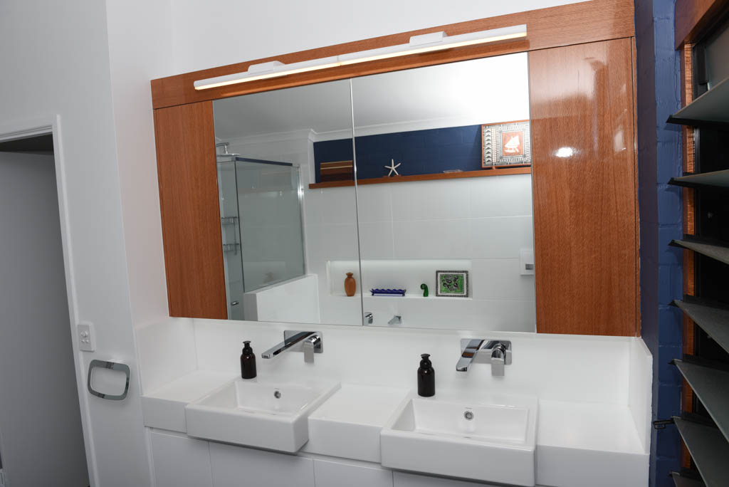 mewald building Renovated Bathroom Featuring Corian Benchtops And Bespoke Cabinetry Made From Natural Finish Silky Oak