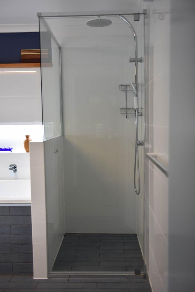 mewald building bathroom with glass shower door and overhead shower head