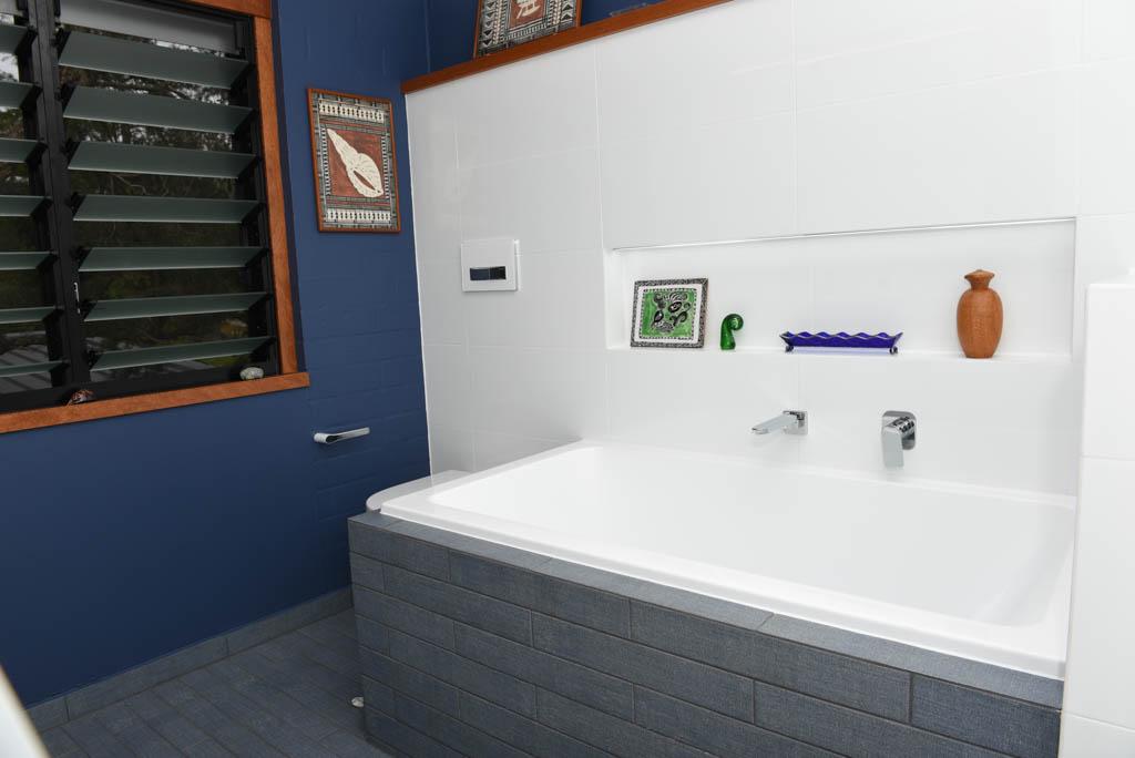 mewald building dark tiled bathroom with navy walls and bathtub