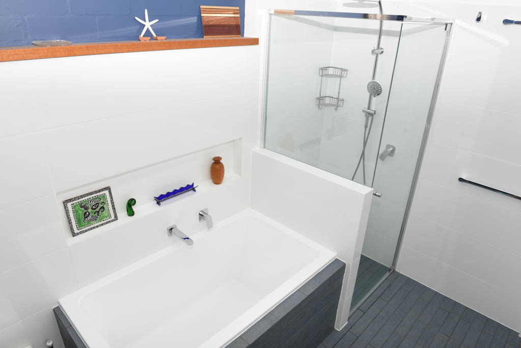 mewald building bathroom with shower and bathtub with grey tiles and white walls