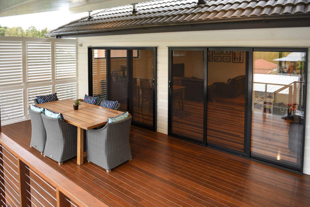 mewald building timber deck with dining table and double entry to interior