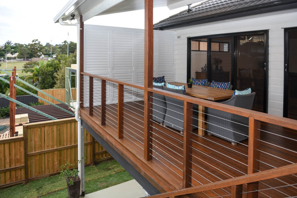 mewald building deck with wired railing and outdoor dining area