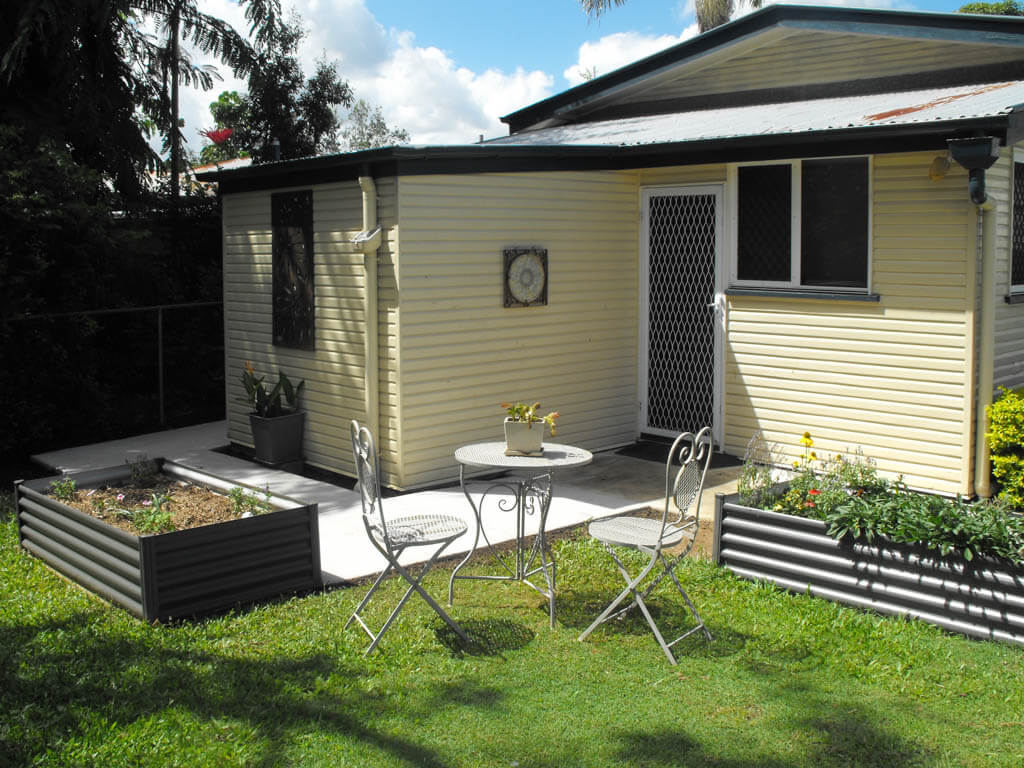 mewald building back of yellow cream home with little patio chairs and table